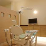 診療室。淡い色のユニット、こちらも間接照明にて和らげる。